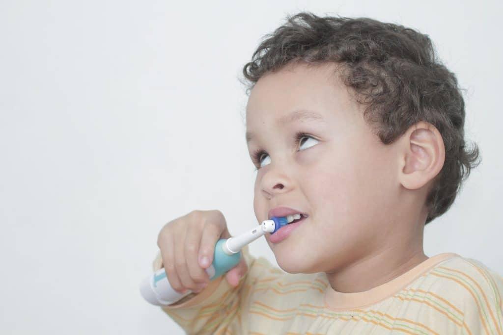 Brosse à dent électrique tenue par un enfant