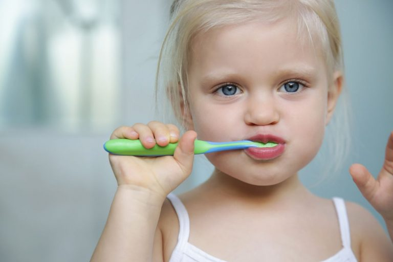 Brosse à dent tenue par une enfant