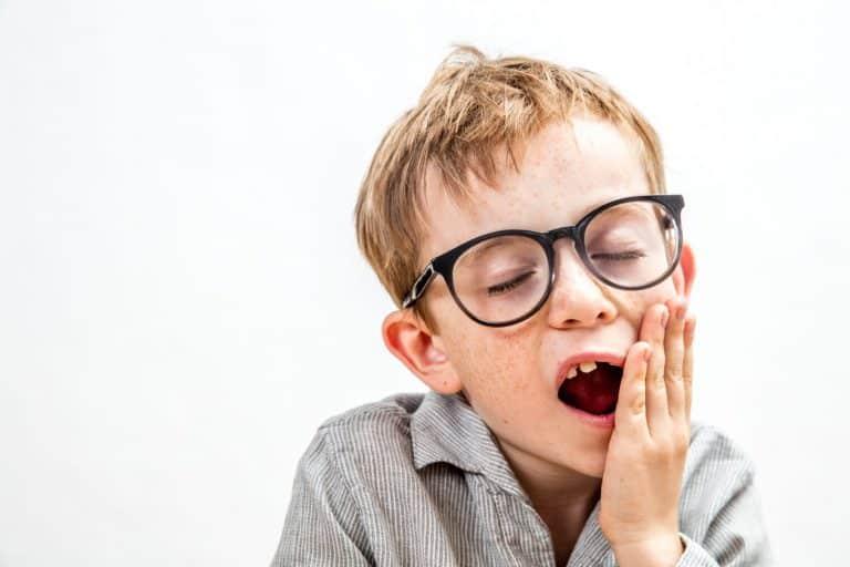 Enfant qui a mal à la mâchoire parce qu'il souffre de bruxisme.